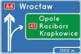 Znak E-1a Tablica przeddrogowskazowa na autostradzie - drogowy kierunku miejscowości - Oznakowanie eksperymentalne dróg szybkiego ruchu